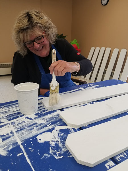 Kathi of the caregiving team painting a float for the Racine 4th of July Parade